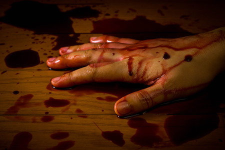 A hand of a dead person soaked in blood on the floor in a murder or suicide scene. Also for Halloween.