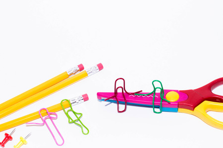 Two paper clips talking, sitting on a zigzag scissors and two lying and talking on pencil. Miniature school life and back to school concept with copy space white background.