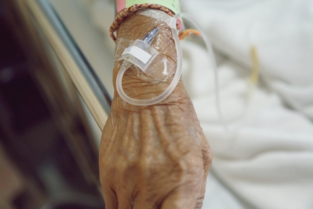 saline solution: old womans hand is on a drip receiving a saline solution.