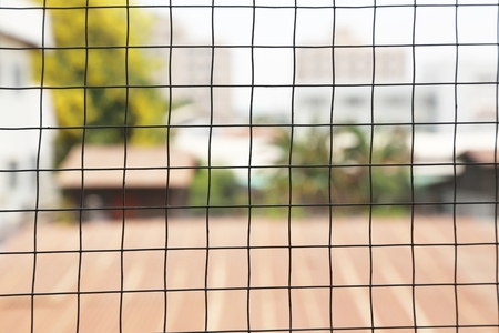 mesh: wire mesh with home and tree blurred background