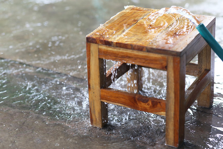 water flow from water hose on wooden chair