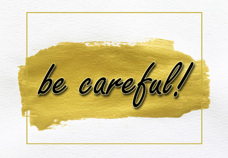 be careful: be careful on gold paint smear stroke stain on white background Stock Photo