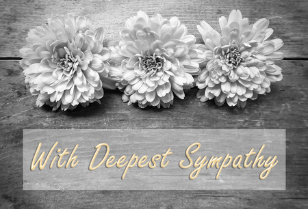 sympathy: flowers on wooden with word With Deepest Sympathy