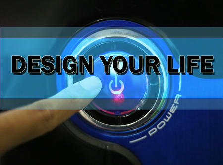 Hand touching button with word 'DESIGN YOUR LIFE'