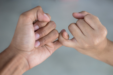 two people with others: hook each others little ; be hand in hand Stock Photo