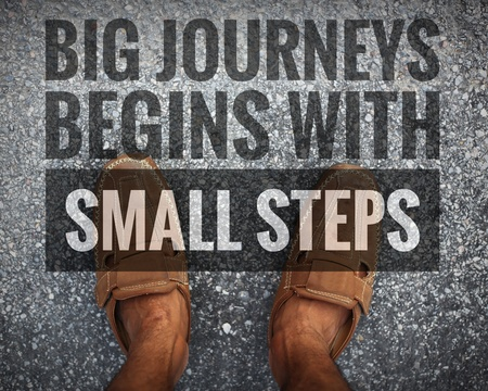 Big journeys begins with small steps words on Man standing on the street Stock Photo
