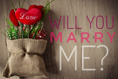 Will you marry me? words on red heart in small sacks and wooden background Stock Photo
