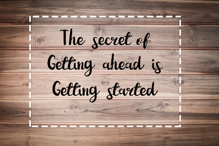 The secret of getting ahead is getting started words on brown wooden wall.