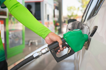 Hand holding fuel nozzle to refuel gasoline for car