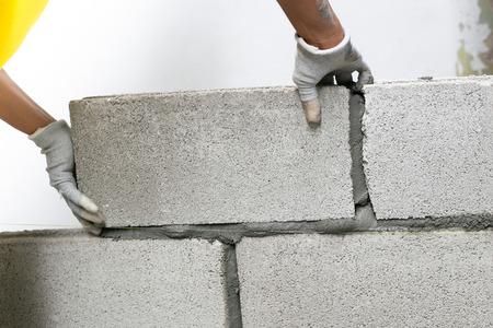 Gros plan sur un maçon industriel installant des briques sur un chantier de construction, construisant des murs. Banque d'images