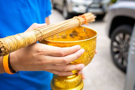 Hand holding pedestal golden tray has been prepared for monk to sprinkle water as a blessing.