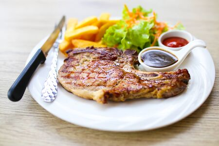 Grilled meat, Porkchops steak with pepper sauce and salad. Stock Photo