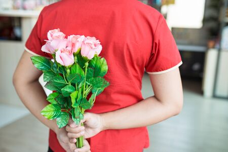 Woman wear red shirt hiding pink rose bouquet on back, for surprise time concept.