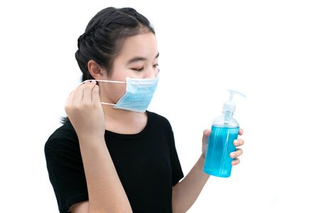 Girl in medical mask cleans hands with antiseptic or alcohol cleansing gel with Do not let virus spread concept. Banco de Imagens