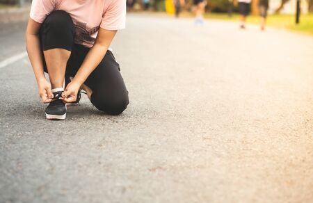 Cheerful runner sitting on floor on city streets. Woman tie shoelaces on road.