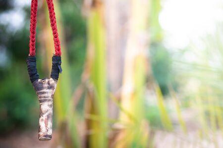 Wood catapult slingshot on natural background.