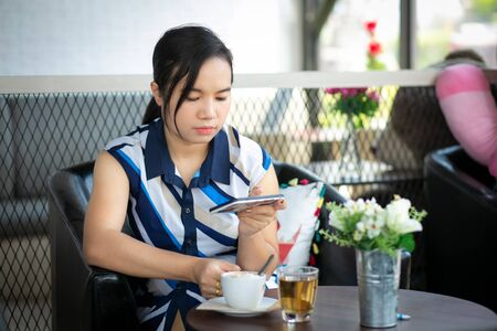 Beautiful woman sitting in a cafe, drinking coffee and using smartphone. 写真素材