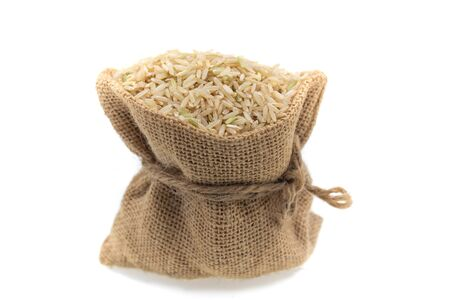 Raw brown rice in brown sack, healthy food background.