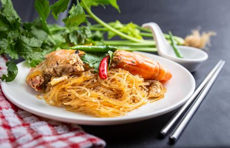 Casseroled prawns with vermicelli on white table or glass noodle bake with shrimp. Shrimp potted with vermicelli. 版權商用圖片