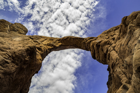 Looking up at massive sandstone arch in Arches National Park, Utah, USA. The eroded red rock arch sits below white clouds and blue skies.