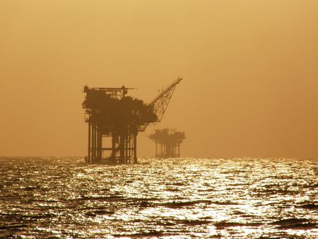 Offshore oil platforms silhouetted by sunset Stock Photo - 3088905