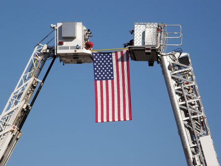 American flag suspended between two fire trucks, for firefighter funeral Stock Photo