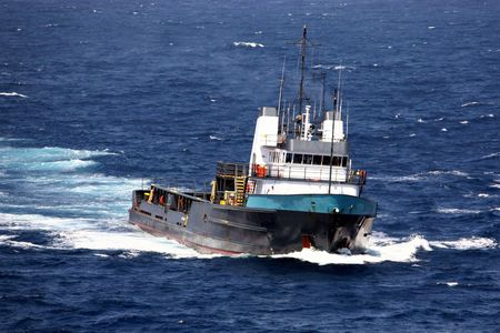 Oilfield supply boat sailing in choppy blue seas