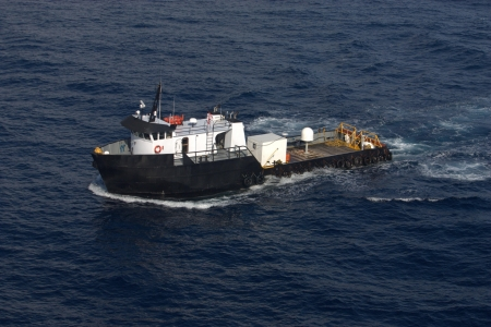 Offshore supply boat carrying cargo on deck for oil platform