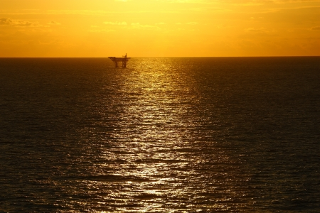 An offshore oil platform in the Gulf of Mexico silhouetted by the sun