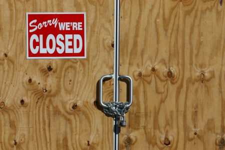 padlocked: Entrance to a business that has closed forever. Glass boarded up, and door chained and padlocked Stock Photo