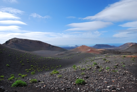 Volcanic mountain landscape in Lanzarote, Canary Islands  Blue sky and clouds in the horizon  Green bushes on the ground  photo