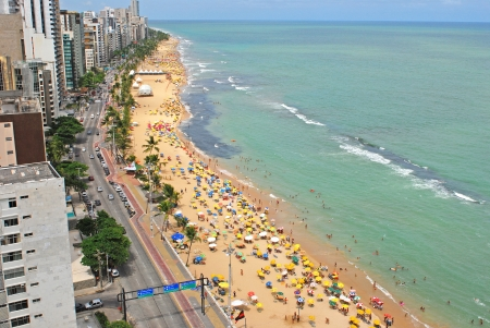 Recife, Pernambuco, Brazil, 2009  A view to the city beach with lots of Brazilian people sunbathing and swimming, and umbrellas, a view from the top of a skyscraper  Stock Photo - 23672796