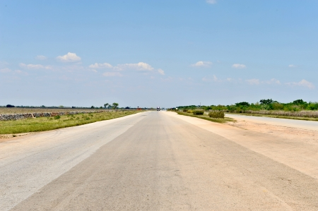 somewhere: A long straight road on a sunny day somewhere in Cuba  Green fields on the sides and blue sky on the top  Stock Photo