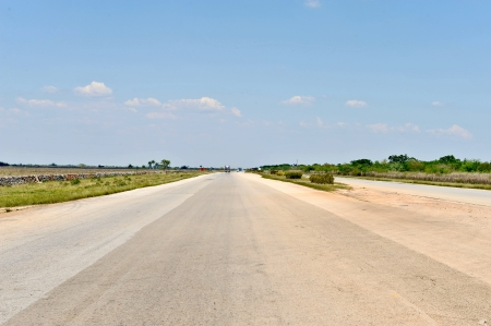 A long straight road on a sunny day somewhere in Cuba  Green fields on the sides and blue sky on the top  photo