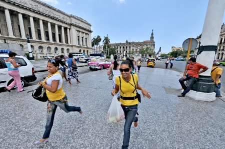 HAVANA, CUBA, MAY 7, 2009  Two women in yellow shirts running on a street in Havana, in front of El Capitolio, in Havana, Cuba, on May 7th, 2009