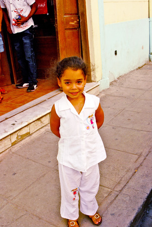 cuba girl: HAVANA, CUBA, MAY 10, 2009  A small girl in the age of five standing in a street in white clothes in Havana, Cuba, on May 10th, 2009