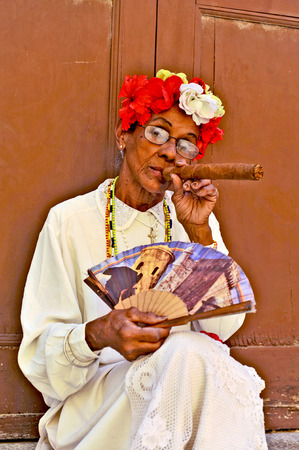 HAVANA, CUBA, MAY 6, 2009  An old woman sitting with a huge cigar in her mouth and roses in her head in Havana, Cuba, on May 7th, 2009