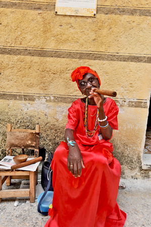 HAVANA, CUBA, MAY 6, 2009  A woman sitting on a bench in the street in a red dress with a huge cigar, in Havana, Cuba, on May 7th, 2009