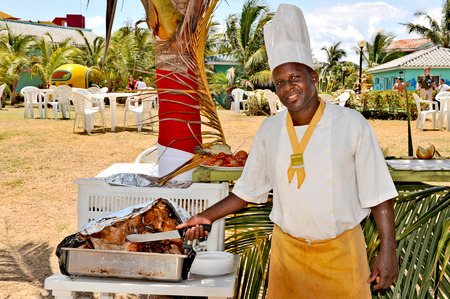 HAVANA, CUBA, MAY 5, 2009  A cook with his kniwe and rosted chicken in a hotel garden in Havana, Cuba, on May 5th, 2009