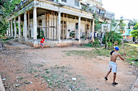 HAVANA, CUBA, MAY 11, 2009  Cuban youngsters playing baseball with primitive equipment in Havana, Cuba, on May 11th, 2009  A metal pipe as the bat and a rock as the ball