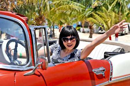 HAVANA, CUBA, MAY 5, 2009  A young Chinese reporter waving out her hand in an old american car, in Havana, Cuba, on May 5th, 2009