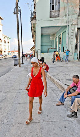 HAVANA, CUBA, MAY 5, 2009  A beautiful young woman walking in a red dress on the street in Havana, Cuba, on May 5th, 2009  Stock Photo - 25693599