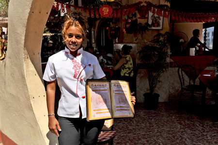HAVANA, CUBA, OCTOBER 20, 2009  A young cuban waitress in a white shirt showing a restaurant menu, in Havana s Chinatown, Havana, Cuba, on October 20th, 2009