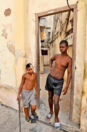20 year old: HAVANA, CUBA, OCTOBER 20, 2009  Two young boys posing in a doorway, in Havana, Cuba, on October 20th, 2009