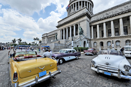 capitolio: HAVANA, CUBA, MAY 11, 2009   Old American cars parked in front of El Capitolio, or National Capitol Building  in Havana, Cuba, on May 11th, 2009