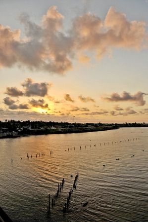 Sun setting down in the outskirts of Havana, Cuba, on May 12th, 2009  Oyster growing site in a river, and wooden stakes from an old dock