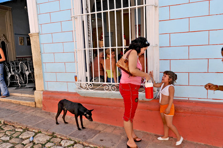 TRINIDAD, CUBA, OCTOBER 27, 2009  A woman, child and a dog in the street in Trinidad, Cuba, on October 27th, 2009