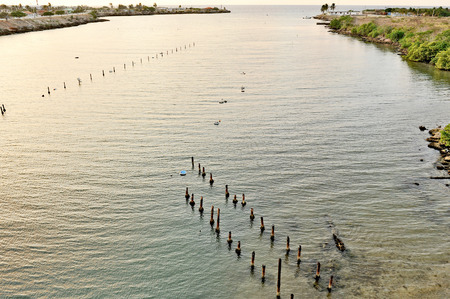 vanished: Sun setting down in the outskirts of Havana, Cuba, on May 12th, 2009  Oyster growing site in a river, and wooden stakes from an old dock