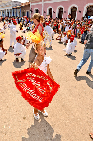 cuba girl: REMEIDOS, CUBA, MAY 7, 2009  A young girl dancing on the street and waving a red flag during a town festival, in Remeidos, Cuba, on May 7th, 2009