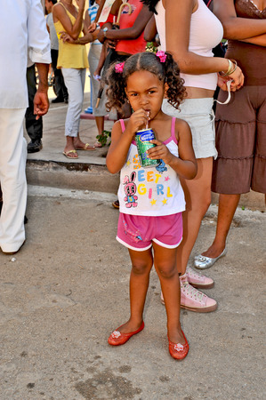 REMEIDOS, CUBA, MAY 7, 2009  A beautiful young girl in the age of five, drinking juice in the middle of a town party, in Remeidos, Cuba, on May 7th, 2009
